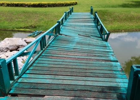 Old wooden green bridge collapses down the stream  Stock Photo