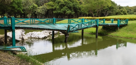 Old wooden green bridge collapses down the stream in the park  Stock Photo