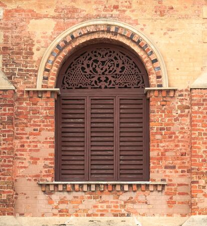 Old Wooden Arch Window on Weathered Brick Wall