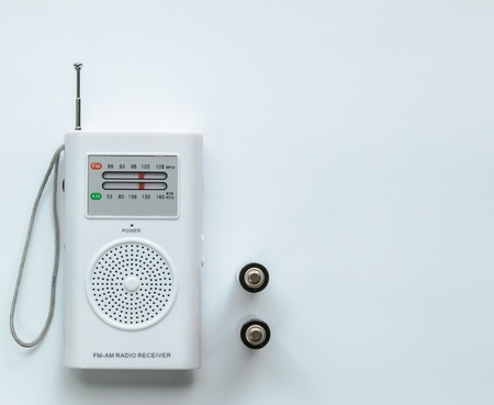 Small white radio receiver with two batteries  white background Stock Photo
