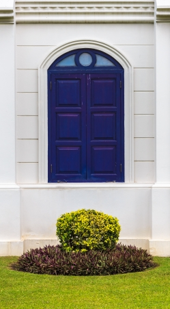 Arch Blue Window of Building with Small Garden
