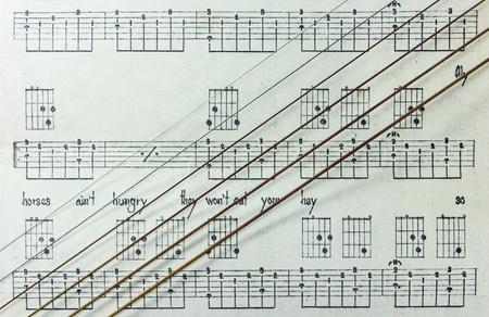 tabulation: Guitar Strings on Old Yellowed Music Sheet with Lyrics, Closeup