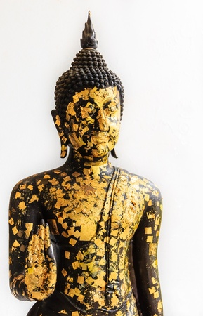 eligion: Black Buddha Statue covered with small Gold Plates isolated on White Background