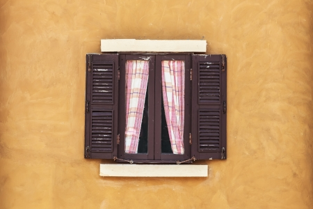 Old Brown Window with Curtain on Yellow Wall