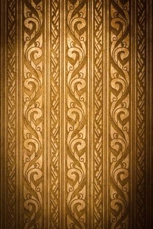 Thai Traditional Carving in Contemporary style on Weathered Gold Plate Background, Vignette photo