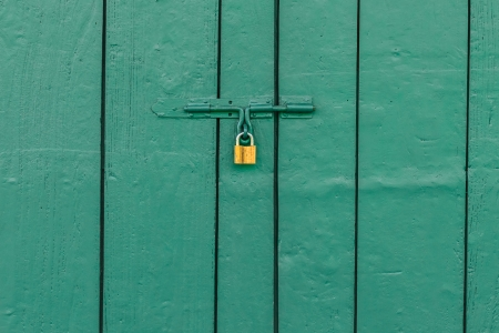 Old Brass Padlock on Wooden Green Door photo