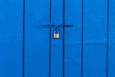 Old Brass Padlock on Wooden Blue Door photo
