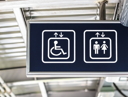 White Elevator Sign on Blue Background, General and Handicap Accessible Elevator, Closeup Stock Photo