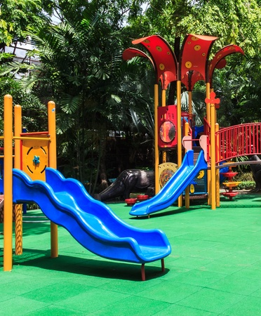 Blue Slides with Green Elastic Rubber Floor for Children in the Park photo