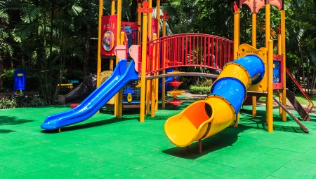 Colorful Playground with Green Elastic Rubber Floor for Children in the Park photo