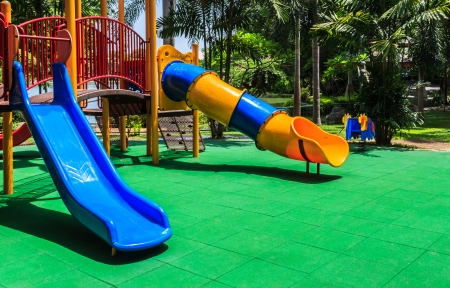 playground equipment: Colorful Playground with Green Elastic Rubber Floor for Children in the Park Stock Photo