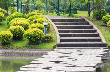 Walkway over Lake Leading to Concrete Steps through the Park
