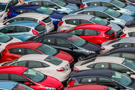 Brand new motor vehicles crowed in a parking lot waiting for distribution to Dealers