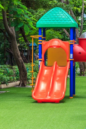 dual: Red Dual Slides for Children on Green Lawn Stock Photo