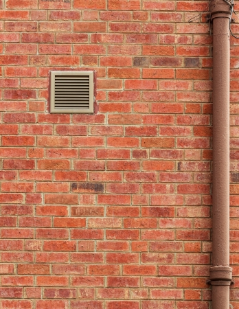 Brown Brick Wall with Vent and Old Pipe photo