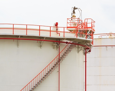 Oil Tank with Vivid Color Pipe and Staircase on White Background photo
