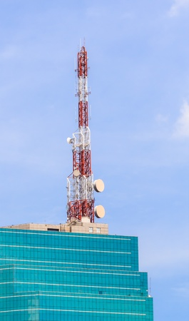 Telecommunication Tower with Antennas on the top of Glass Building