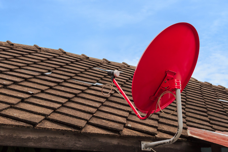 Red Satellite TV Receiver Dish on the Old Tiles Roof photo