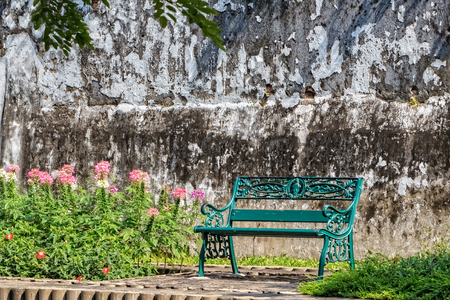 Green Bench in Sunshine Morning with Old Wall Background