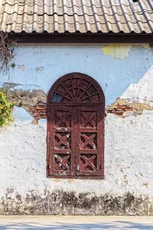 Facade of Old Wooden Arch Window on Ruined White Building