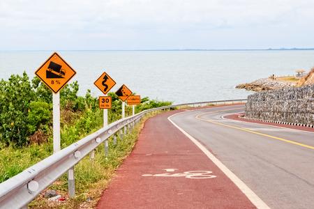 steep cliff sign: Downhill Winding Road wih Bike Lane Stock Photo