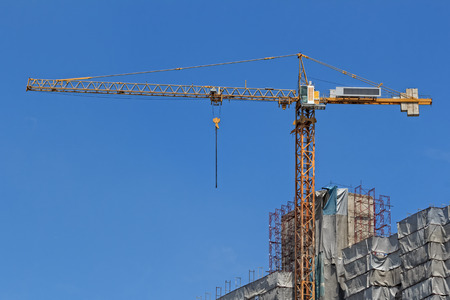 Yellow Construction Crane against Blue Sky Background
