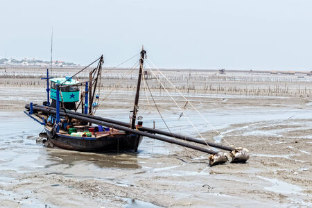 ebb: Fishing boat at ebb tide waiting for the flood tide, Thailand