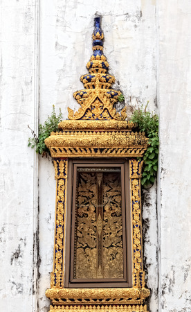 Old Thai Traditional Window in Temple on Weathered White Wall Stock Photo