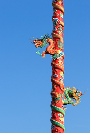 Twin Dragons on Red Pillar isolated on Blue Sky  photo