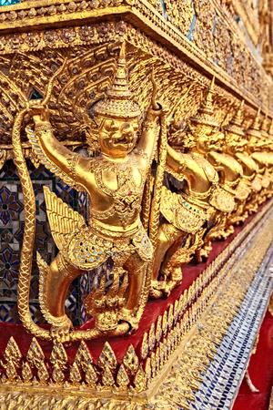 Golden Statue of Garuda catching Naga around Pavillion of Wat Phra Kaew Temple, Bangkok, Thailand photo