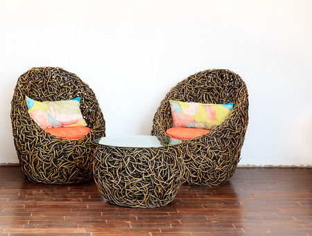 Round Wicker Chairs with Glass Table and Colorful pillows photo