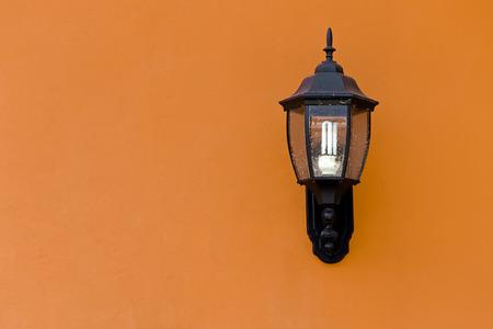 Old Lantern on Yellow Concrete wall with saving energy bulb, Closeup Stock Photo