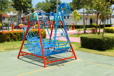 Blue swings in Viking ship pattern in playground