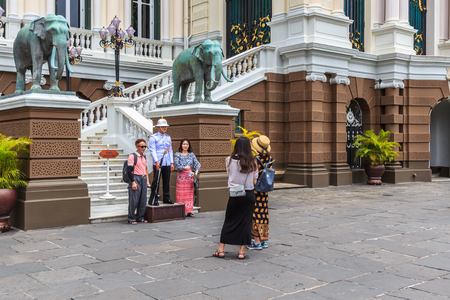 BANGKOK - JUNE 27: Unidentified Asian tourists take a picture with the Thai Royal Guard at Chakri Maha Prasat Hall during their tour in the Grand Palace, on June 27, 2016 in Bangkok, Thailand. Editorial
