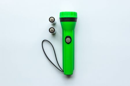 Green Flashlight with Battery on White Background