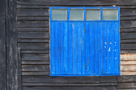 Old Blue Window on Weathered Wooden Wall Stock Photo