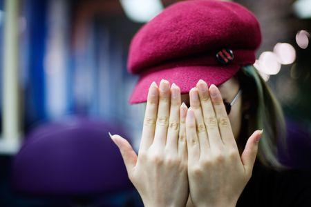 hides: Girl hides face behind hands