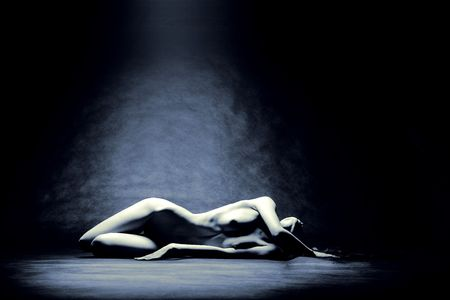 Studio shot of nude model laying in pool of light Stock Photo - 701891