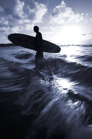 Silhouette of surfer coming in to the beach at sunset