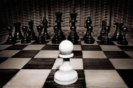 steadfast: Close up shot of white pawn against whole of black army Stock Photo