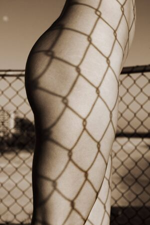 bodyscape: Close up body part shot of leg and bum with shadow pattern of fence Stock Photo