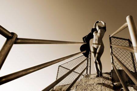 Desnuda modelo en la parte superior de las escaleras en busca estirar hasta  Foto de archivo