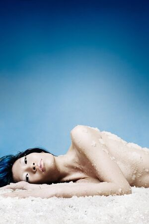 Asian girl laying on bed of ice Stock Photo - 716332