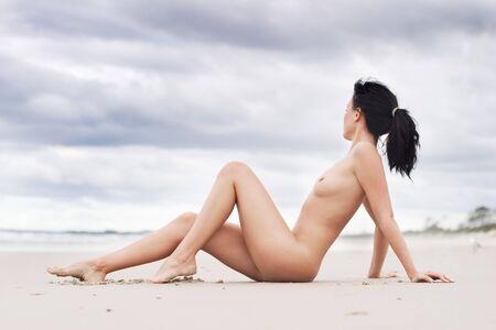 mujer desnuda sentada: Desnudo mujer sentada en la playa  Foto de archivo