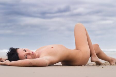 Nude model stretches out on beach Stock Photo - 801689