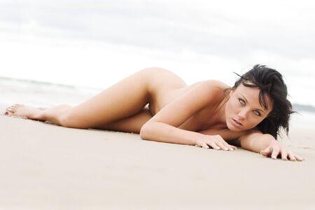 Mujer desnuda en la playa, por la que se  Foto de archivo