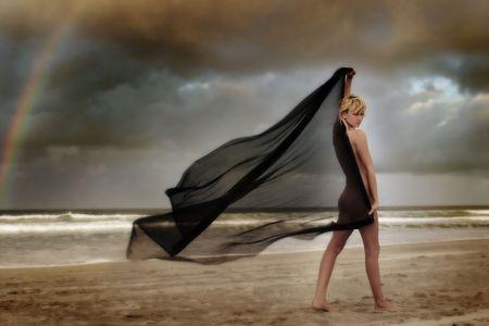 Un modelo plantea en la playa con algunos arrastrados por el viento tejido  Foto de archivo