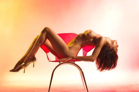 Nude model draped across red chair in studio