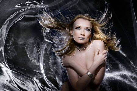 Nude girl in studio with silver cloth blowing around