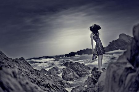 stranded: A woman is stranded on the rocks of a beach